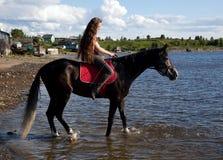 Ein Mädchen mit dem flüssigen Haar auf einem schwarzen Pferd Lizenzfreie Stockbilder