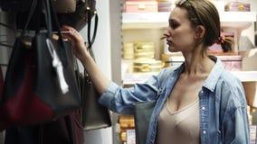 Ein Mädchen mit dem Haar in einem Bündel und den Gläsern auf ihrem Kopf wählt eine Tasche Zusammenstellung von Lederhandtaschen i stock video