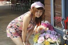 Ein Mädchen mit dem Hutbereitstehen mit Blumen lizenzfreie stockbilder