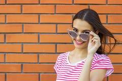 Ein Mädchen mit dem langen braunen Haar, das ein rotes und weißes gestreiftes T-Shirt trägt, schaut beiseite bei der Stellung auf Stockfoto