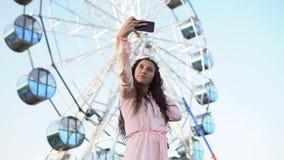 Ein Mädchen mit dem langen Haar in einem Kleid macht selfie unter Verwendung eines Smartphone, der nahe dem Riesenrad steht 4K stock video footage