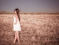 Ein Mädchen mit dem langen Haar in einem weißen Kleid Lizenzfreie Stockfotos