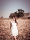 Ein Mädchen mit dem langen Haar in einem weißen Kleid, das auf einem Sommergebiet aufwirft Stockfoto
