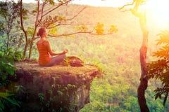 Ein Mädchen mit dem Rucksack, der auf der Klippe sitzt und sich hoch in m entspannt lizenzfreie stockfotos