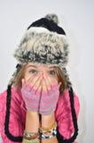 Ein Mädchen mit den Händen auf Gesicht und einem lustigen Hut Lizenzfreies Stockfoto