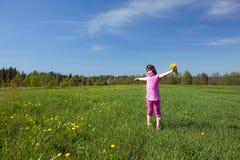 Ein Mädchen mit einem Blumenstrauß auf einer Wiese Lizenzfreie Stockfotos