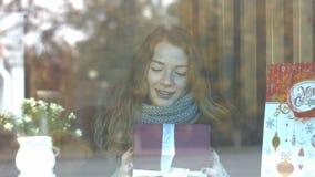 Ein Mädchen mit einem Geschenk in einem Café stock footage