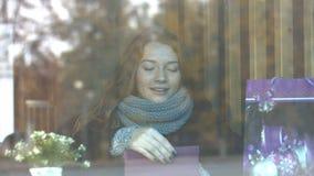 Ein Mädchen mit einem Geschenk in einem Café stock video