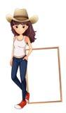 Ein Mädchen mit einem Hut, der vor dem leeren Brett steht Stockfoto