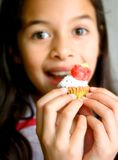 Ein Mädchen mit einem kleinen kleinen Kuchen abgedeckt beim Bereifen. stockfotos