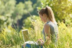 Ein Mädchen mit einem Laptop in der Natur unter dem grünen Gras stockfotografie