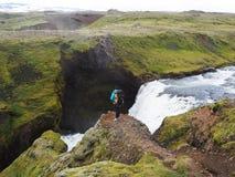 Ein Mädchen mit einem Rucksack steht über einer Schlucht mit einem Wasserfall Stockbilder