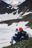 Ein Mädchen mit einem Rucksack wird unter Verwendung ihres Smartphone fotografiert lizenzfreies stockbild