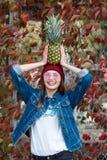 Ein Mädchen mit einer Ananas steht auf der Straße auf einem Herbsthintergrund Lizenzfreie Stockfotos