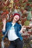 Ein Mädchen mit einer Ananas steht auf der Straße auf einem Herbsthintergrund Stockfotos