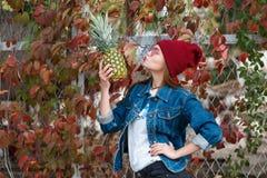 Ein Mädchen mit einer Ananas steht auf der Straße auf einem Herbsthintergrund Lizenzfreie Stockbilder