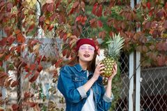 Ein Mädchen mit einer Ananas steht auf der Straße auf einem Herbsthintergrund Lizenzfreies Stockfoto