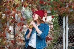 Ein Mädchen mit einer Ananas steht auf der Straße auf einem Herbsthintergrund Stockfotografie
