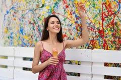 Ein Mädchen mit einer Eiscreme lächelt und bewegt in den Abstand wellenartig Stockfoto
