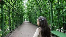 Ein Mädchen mit einer Krone auf ihrem Kopf geht in den Sommergarten stock video footage