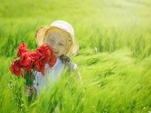 Ein Mädchen mit einer positiven Aussicht mit einem Blumenstrauß von Mohnblumen auf einem Gebiet des Grünroggens Lizenzfreie Stockfotos