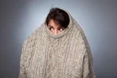 Ein Mädchen mit einer sozialen Phobie versteckt ihr Gesicht in einer Strickjacke Lizenzfreie Stockfotografie