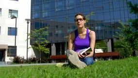 Ein Mädchen mit Gläsern liest ein Buch stock video