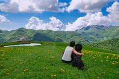 Ein Mädchen mit ihrem großen Hund betrachtet die Landschaft in den Bergen stockfotografie