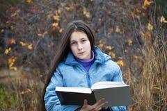 Ein Mädchen mit ihrem Haar ein Buch lesend Stockfotos