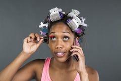 Ein Mädchen mit Lockenwicklern in ihrem Haar sprechend am Telefon lizenzfreie stockbilder