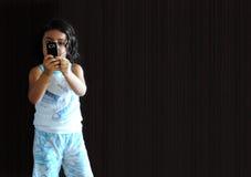 Ein Mädchen mit Telefon Stockbild