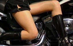 Ein Mädchen mit weicher Haut auf dem schwarzen Motorrad Stockfotografie