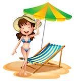 Ein Mädchen nahe einem faltbaren Strandbett und -regenschirm Stockbild