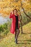 Ein Mädchen nahe einem Fluss und einem Baum mit Gelb verlässt in einem roten Mantel und ein schwarzes Kleid justiert ihr Haar Lizenzfreies Stockbild