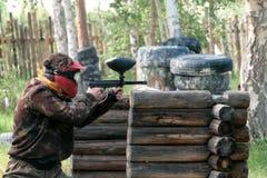 Ein Mädchen oder ein Kerl in einer Gesichtsmaske- und Tarnungsuniform mit einer Waffe in ihren Händen strebt den Feind wegen des  stockfotografie