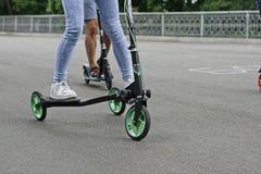 Ein Mädchen reitet einen Roller Stockfoto