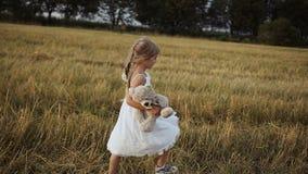 Ein Mädchen ` s Schuh in einer Miezekatze und in einem weißen Kleid gekleidet geht auf das Feld und wird durch einen Spielzeugbär stock video footage