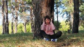 Ein Mädchen setzt Kopfhörer auf ihren Kopf und hört Musik auf ihrem Smartphone Das Konzept von Musik und Erholung von im Freien stock video footage