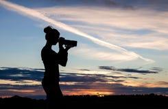 Ein Mädchen silhouettiert gegen einen Sonnenunterganghimmel, ein Foto mit einem DSLR machend lizenzfreie stockfotos