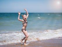 Ein Mädchen singt einen fröhlichen Tanz in der Sonne durch das Meer Lizenzfreies Stockbild