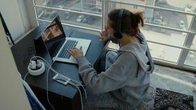 Ein Mädchen sitzt auf dem Balkon mit einem Laptop stock video footage
