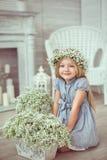 Ein Mädchen sitzt auf dem Boden nahe den Blumen Lizenzfreie Stockfotografie