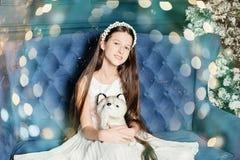 ein Mädchen sitzt auf der Couch im Studio Neues Jahr und Weihnachten Umarmungshundespielzeug lizenzfreie stockfotos