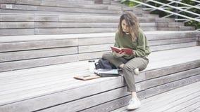 Ein Mädchen sitzt auf der Treppe ein Buch lesend stockbild