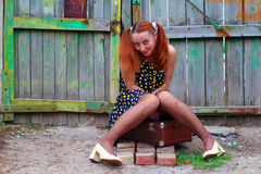 Ein Mädchen sitzt auf einem Koffer Stockbilder