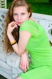 Ein Mädchen sitzt auf einer Bank im Park Lizenzfreies Stockfoto