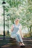 Ein Mädchen sitzt auf einer Bank mit einem Zweig von Kirschblüten herein lizenzfreies stockfoto