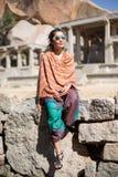 Ein Mädchen sitzt auf einer Steinwand Lizenzfreies Stockbild