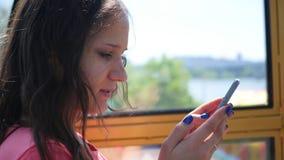 Ein Mädchen sitzt mit einem Telefon in einem Vergnügungspark macht herein ein selfie Stockbilder
