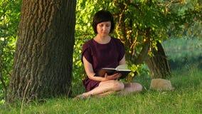 Ein Mädchen sitzt nahe einem Baum und liest ein Buch stock video footage